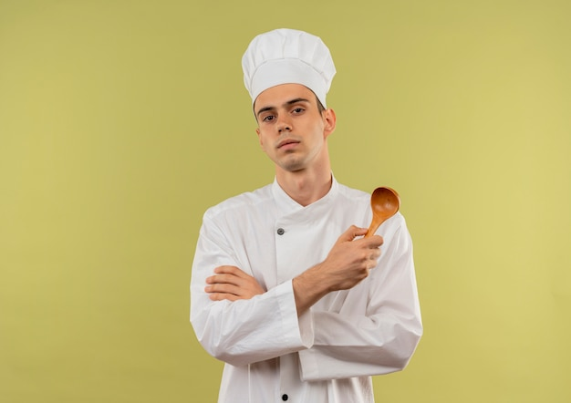 Confident young male cook wearing chef uniform crossing hands holding spoon on isolated green wall with copy space