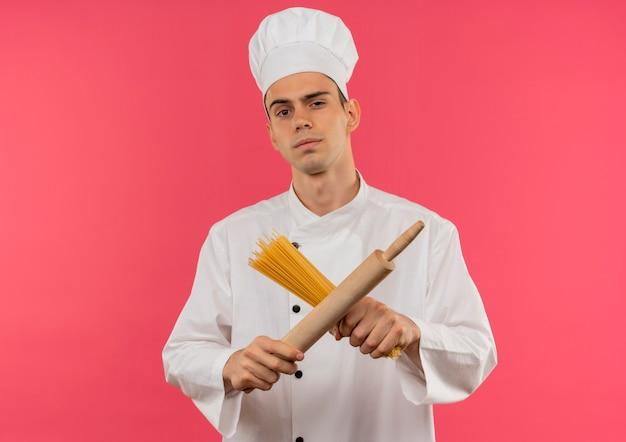 Уверенный молодой мужчина-повар в униформе шеф-повара пересекает скалку и спагетти на изолированной розовой стене