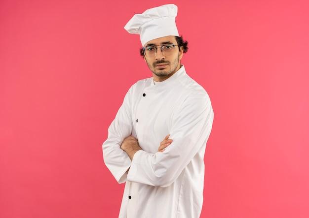 Fiducioso giovane cuoco maschio indossa uniforme da chef e occhiali che attraversano le mani