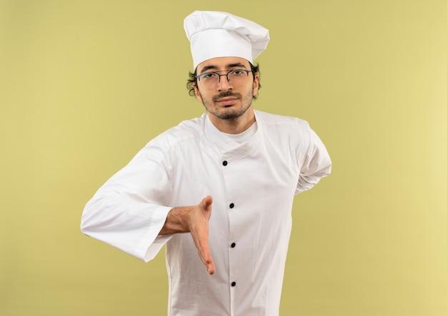 Fiducioso giovane cuoco maschio indossa uniforme da chef e bicchieri tendendo la mano