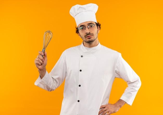 Fiducioso giovane cuoco maschio che indossa l'uniforme dello chef e bicchieri tenendo la frusta e mettendo la mano sul fianco