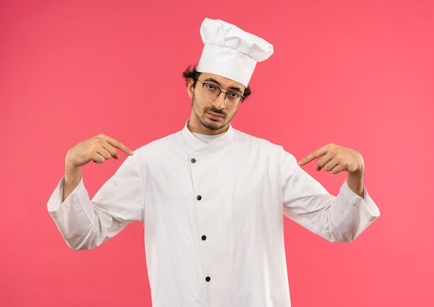Fiducioso giovane cuoco maschio che indossa l'uniforme dello chef e gli occhiali indica se stesso