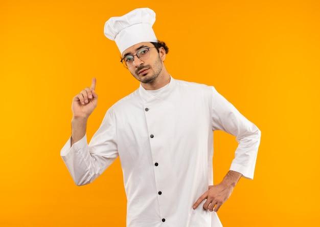 Fiducioso giovane cuoco maschio che indossa l'uniforme dello chef e gli occhiali punta verso l'alto e mette la mano sul fianco