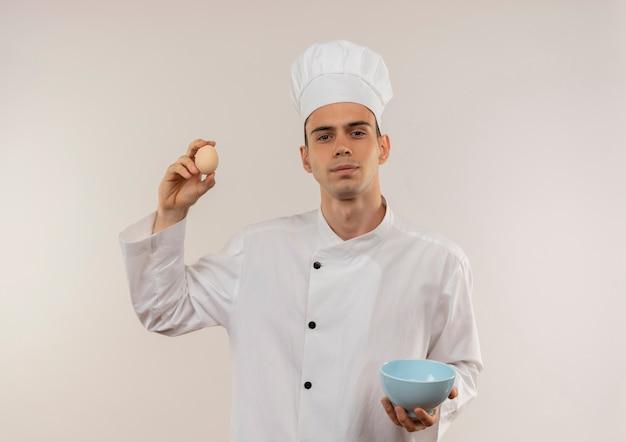 Fiducioso giovane cuoco maschio indossando chef uniforme tenendo la ciotola e l'uovo sulla parete bianca isolata