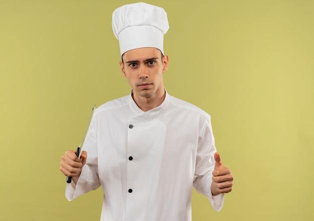 コピースペースのある孤立した緑の壁にクリーバーを親指で持ち上げるシェフの制服を着た自信を持って若い男性料理人