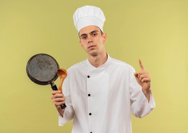 孤立した緑の壁にジェスチャーを示すフライパンとスプーンを保持しているシェフの制服を着て自信を持って若い男性料理人