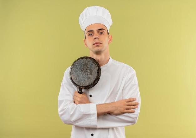 コピースペースと孤立した緑の壁にフライパンの交差点の手を保持しているシェフの制服を着て自信を持って若い男性料理人