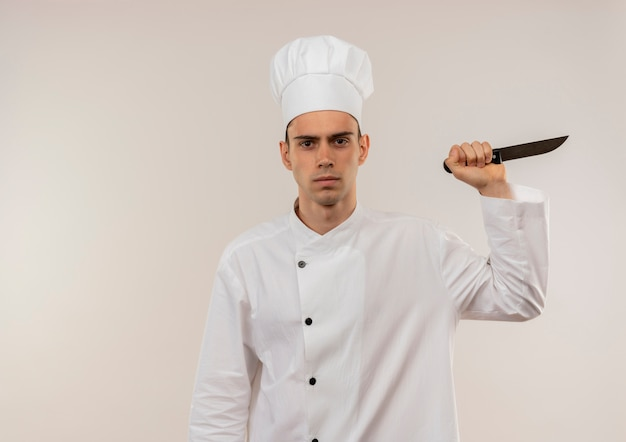 コピースペースと孤立した白い壁にナイフを保持しているシェフの制服を着て自信を持って若い男性料理人