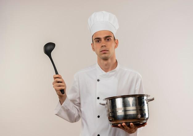 孤立した白い壁に鍋とおたまを保持しているシェフの制服を着て自信を持って若い男性料理人