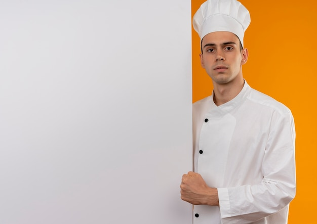 Confident young male cool wearing chef uniform holding white wall doing strong gesture on isolated yellow wall with copy space