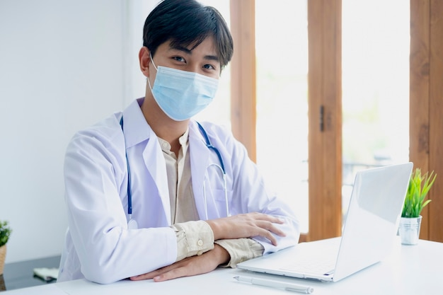 Confident young male doctor at office desk.