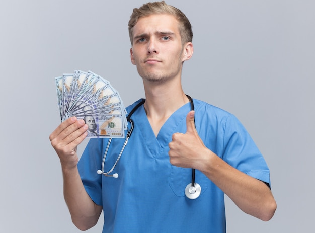 Confident young male doctor wearing doctor uniform with stethoscope holding cash showing thumb up isolated on white wall