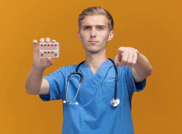 오렌지 벽에 고립 된 제스처를 보여주는 약을 들고 청진기로 의사 유니폼을 입고 자신감 젊은 남성 의사