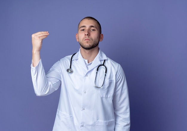 Confident young male doctor wearing medical robe and stethoscope around his neck pretend holding something and looking isolated on purple  with copy space