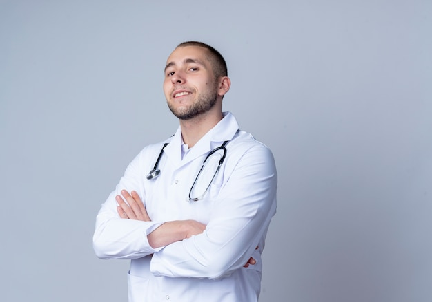 Confident young male doctor wearing medical robe and stethoscope around his neck standing with closed posture and smiling isolated on white  with copy space