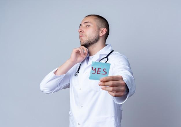 Fiducioso giovane medico maschio che indossa veste medica e stetoscopio intorno al collo allungando la nota di sì verso la telecamera e toccando il mento isolato su bianco con lo spazio della copia