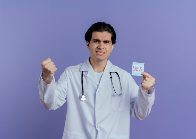 Confident young male doctor wearing medical robe and stethoscope showing yes note  doing be strong gesture isolated on purple wall with copy space