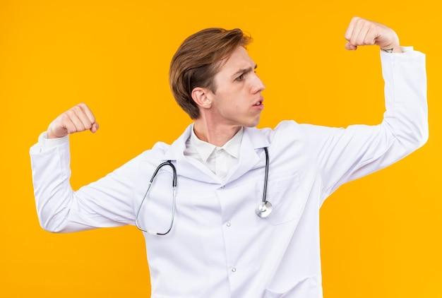 Fiducioso giovane medico maschio che indossa un abito medico con uno stetoscopio che mostra un gesto forte