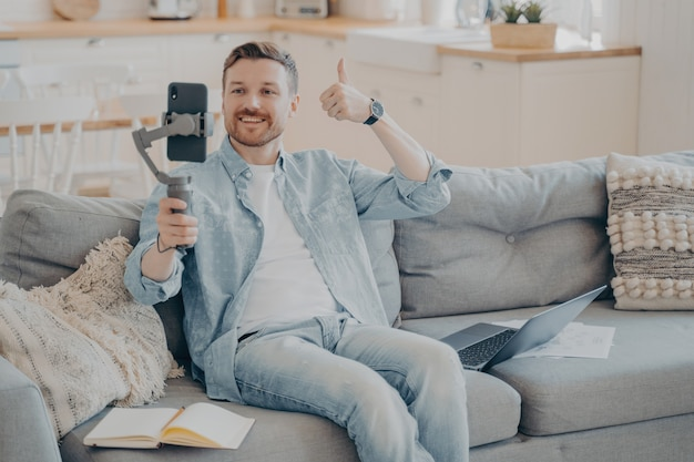 Confident young male freelancer showing thumbs up gesture to his client to inform him that everything is going well through phone video call, sitting on couch holding gimbal with phone
