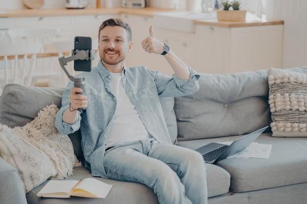 自信を持って若い男性のフリーランサーがクライアントに親指を立てるジェスチャーを見せて、電話でジンバルを持ってソファに座って、電話のビデオ通話ですべてが順調に進んでいることを知らせます