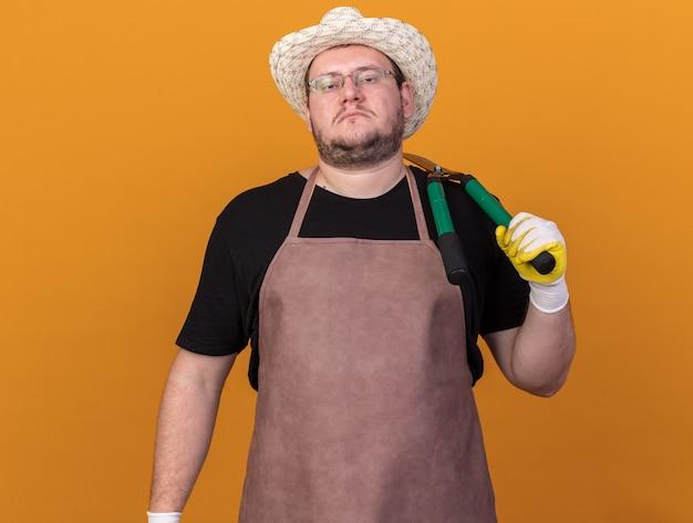 Уверенный молодой мужчина-садовник в садовой шляпе и перчатках держит ножницы на плече, изолированные на оранжевой стене