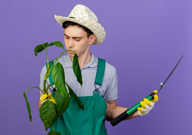 ガーデニングの帽子と手袋を身に着けている自信を持って若い男性の庭師はクリッパーを保持し、植物を見て