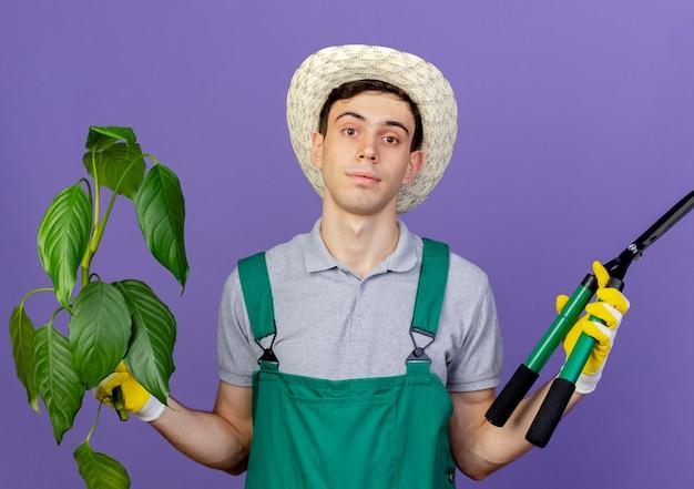 ガーデニングの帽子と手袋を身に着けている自信を持って若い男性の庭師は、植物とクリッパーを保持します