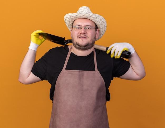 Fiducioso giovane giardiniere maschio indossando guanti e cappello da giardinaggio tenendo vanga sulla spalla isolata sulla parete arancione