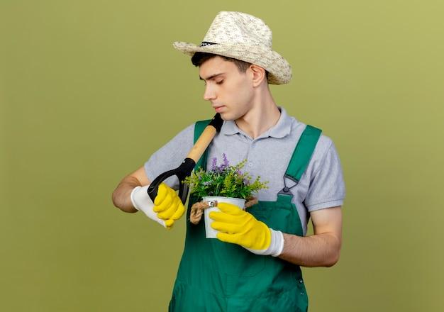 Fiducioso giovane giardiniere maschio indossando guanti e cappello da giardinaggio tiene vanga sulla spalla e fiori in vaso di fiori