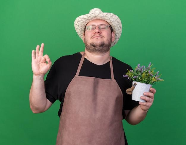 Giovane giardiniere maschio sicuro che indossa il cappello di giardinaggio che tiene fiore in vaso da fiori che mostra gesto giusto isolato sulla parete verde
