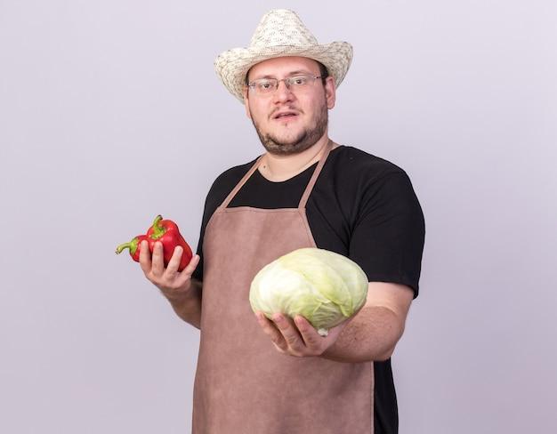 Fiducioso giovane giardiniere maschio che indossa cappello da giardinaggio tenendo i peperoni tenendo fuori il cavolo alla telecamera isolata sul muro bianco