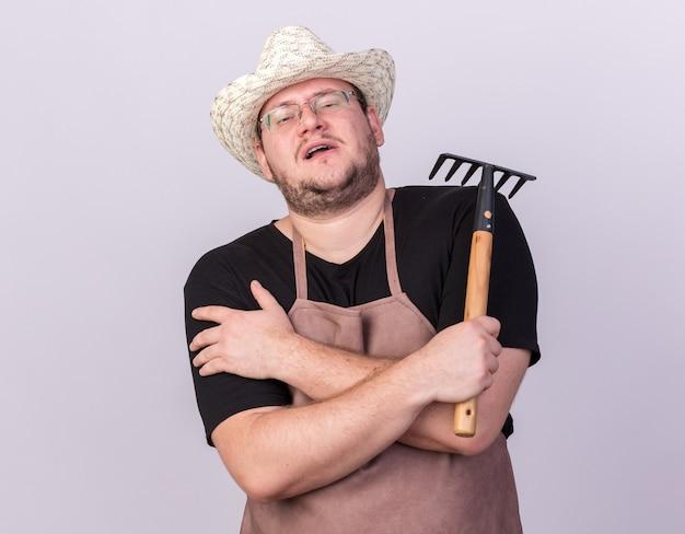 Уверенный молодой мужчина-садовник в садовой шляпе держит грабли, скрещивая руки, изолированные на белой стене