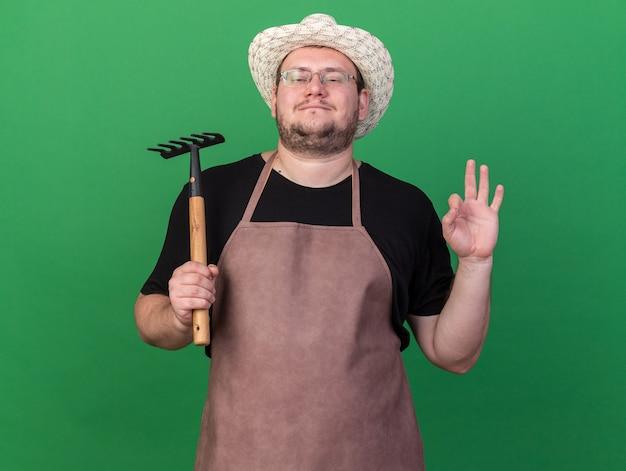 緑の壁に分離された大丈夫なジェスチャーを示す肩に熊手を保持しているガーデニング帽子を身に着けている自信を持って若い男性の庭師