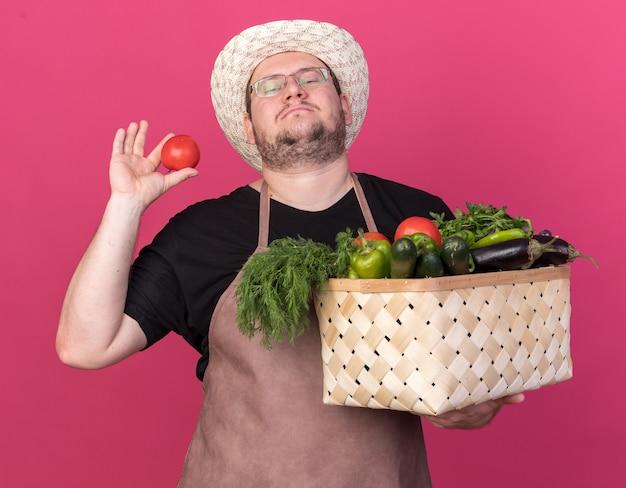 Fiducioso giovane giardiniere maschio che indossa il cappello di giardinaggio che tiene cestino di verdure e pomodoro isolato sulla parete rosa