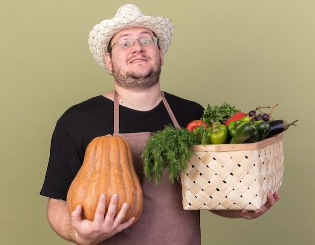 Уверенный молодой мужчина-садовник в садовой шляпе держит корзину с овощами с тыквой, изолированную на оливково-зеленой стене
