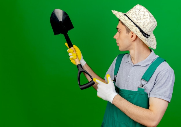 ガーデニング帽子をかぶって自信を持って若い男性の庭師は、コピースペースで緑の背景に分離されたスペードを保持し、ポイントします