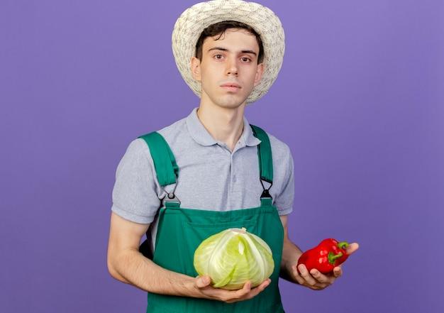 ガーデニング帽子をかぶって自信を持って若い男性の庭師はキャベツとピーマンを保持します