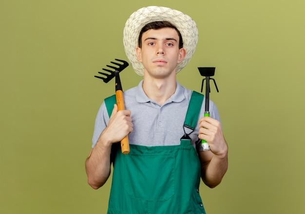 Il giovane giardiniere maschio sicuro che porta il cappello di giardinaggio tiene il rastrello e il rastrello della zappa