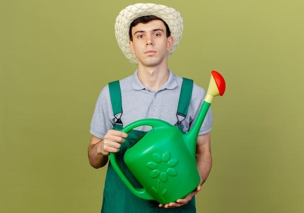 원예 모자를 쓰고 자신감 젊은 남성 정원사는 물을 수 보유