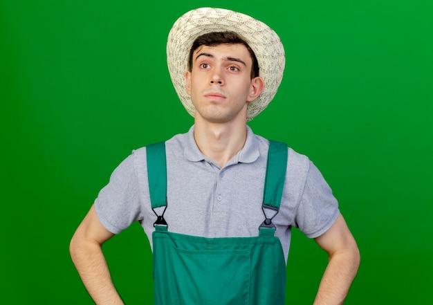 ガーデニング帽子をかぶって自信を持って若い男性の庭師は、コピースペースで緑の背景に分離された側を見て腰に手を置きます