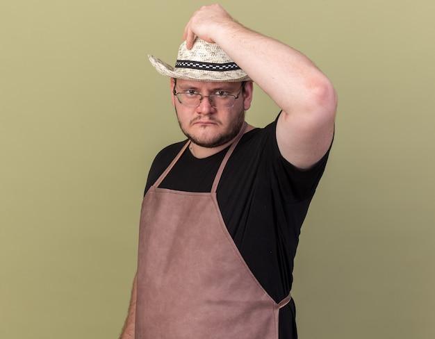 올리브 녹색 벽에 고립 된 머리에 손을 넣어 원예 모자를 쓰고 자신감 젊은 남성 정원사