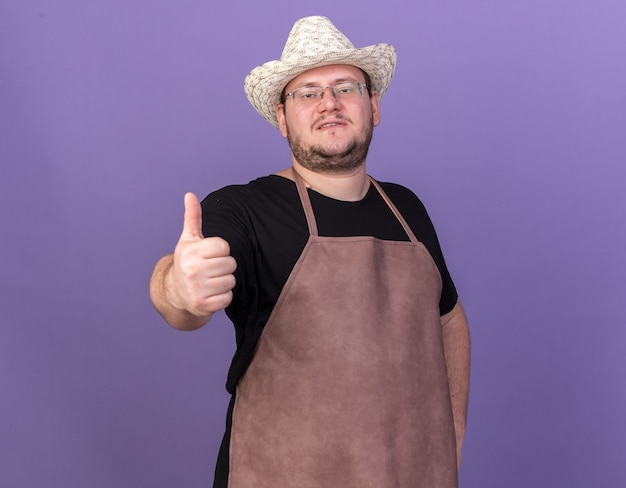 青い壁に分離された親指を示すガーデニング帽子をかぶって自信を持って若い男性の庭師