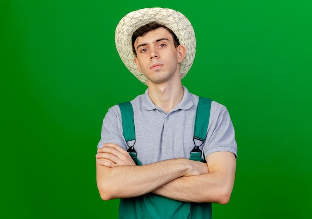 ガーデニング帽子をかぶって自信を持って若い男性の庭師は、コピースペースで緑の背景に分離された腕を組んで立っています