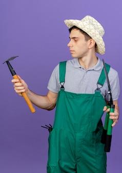 Fiducioso giovane giardiniere maschio che indossa cappello da giardinaggio sta con attrezzi da giardinaggio guardando rastrello isolato su sfondo viola con spazio di copia