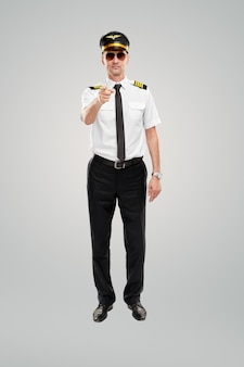 Confident young male pilot pointing at camera against gray background