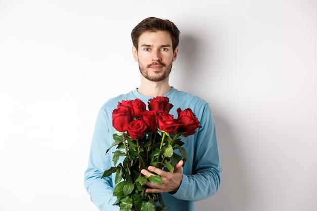 Уверенный молодой человек приносит цветы на дату дня святого валентина, держа романтический букет, стоя на белом фоне.
