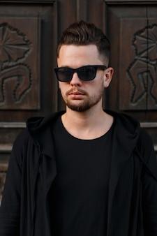 검은 세련 된 안경과 빈티지 나무 문 근처 검은 유행 옷에 자신감 젊은 남자 hipster 남자