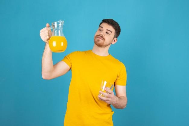 Уверенно молодой человек держит графин со свежим апельсиновым соком и смотрит на него.