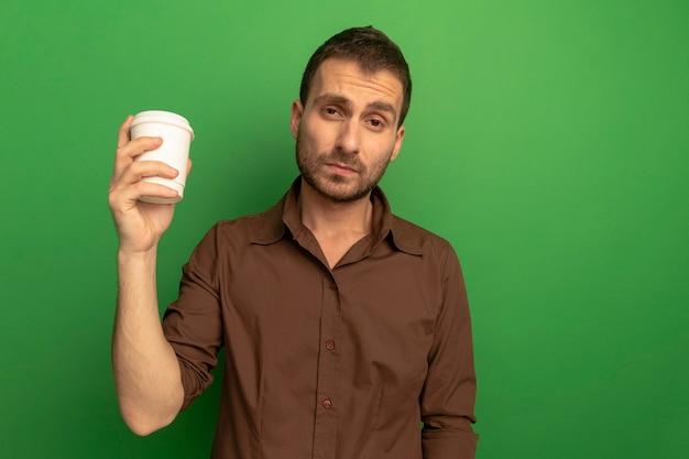 緑の壁で隔離の正面を見てプラスチック製のコーヒーカップを保持している自信を持って若い男