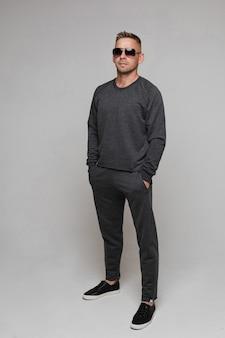 Уверенный молодой человек в черных очках, стоя с руками в карманах. изолированное фото серого фона. концепция моды